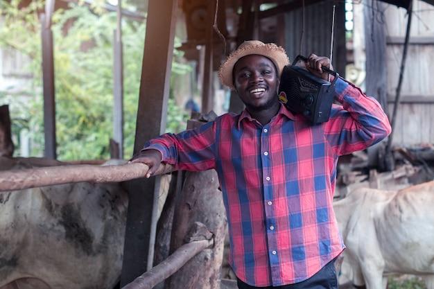Afrikanischer landwirtmann mit retro- radiosendungsempfänger auf schulter steht das glückliche lächeln, das auf altem kuhstallhintergrund im freien ist