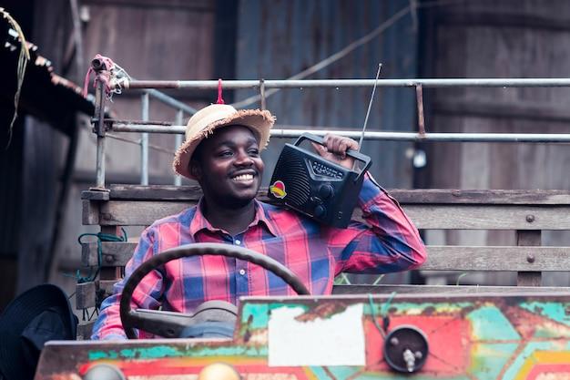 Afrikanischer landwirtmann mit retro- radiosendungsempfänger auf schulter steht das glückliche lächeln, das auf altem traktorhintergrund im freien ist