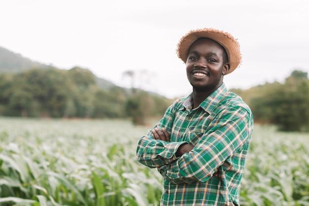 Afrikanischer landwirtmannstand am grünen bauernhof mit glücklichem und lächeln.