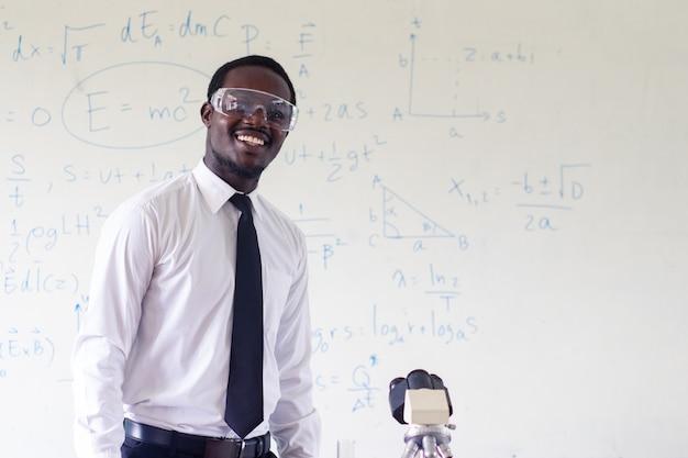 Afrikanischer lehrer der wissenschaft, der vor der tafel steht, die schüler im klassenzimmer unterrichtet