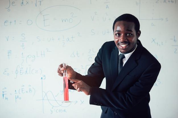 Afrikanischer lehrer, der wissenschaft in der stammklasse unterrichtet.