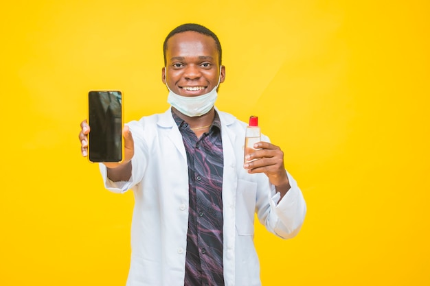 Afrikanischer männlicher arzt trägt eine schutzmaske, die ein händedesinfektionsmittel hält und a