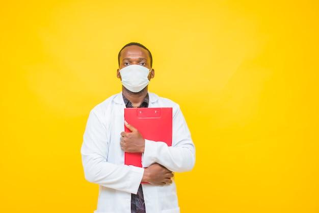 Afrikanischer männlicher arzt trägt eine schutzmaske und hält einen medizinischen bericht