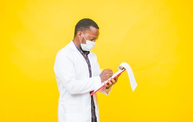 Afrikanischer männlicher arzt trägt eine schutzmaske, während er einen medizinischen bericht überprüft