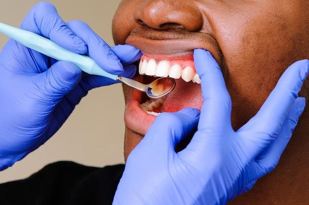 Afrikanischer männlicher patient, der zahnmedizinische behandlung in der zahnmedizinischen klinik erhält