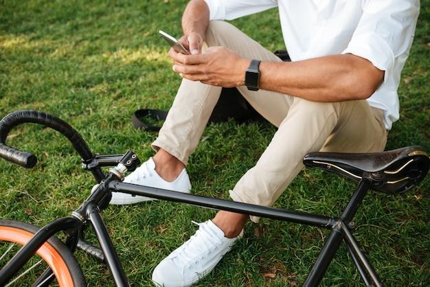 Afrikanischer mann am frühen morgen mit fahrrad, das handy hält