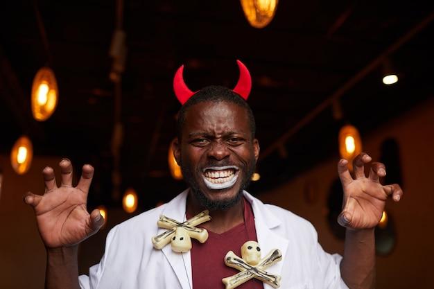 Afrikanischer mann bei der halloween-party im nachtclub