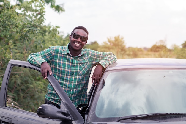 Afrikanischer mann, der auf der straße nahe geöffneter tür seines autos steht.