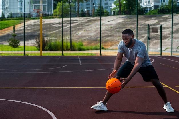 Afrikanischer mann, der ball auf basketballplatz schlägt
