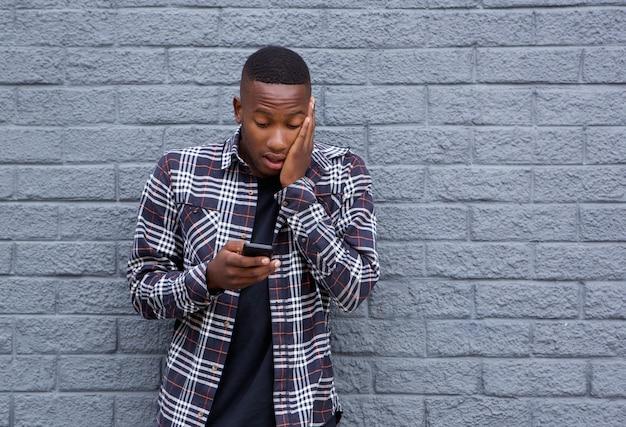 Afrikanischer mann, der beim lesen einer textnachricht überrascht schaut