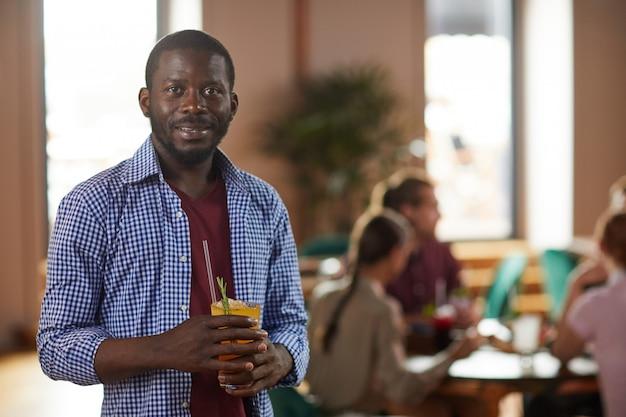 Afrikanischer mann, der cocktail-getränk hält