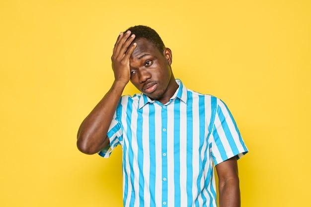 Afrikanischer mann, der den kopf mit der hand und dem blauen hemdmodell berührt, beschnittene ansicht. foto in hoher qualität
