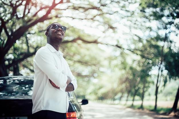 Afrikanischer mann, der ein weißes hemd und eine sonnenbrille das auto bereitstehen trägt