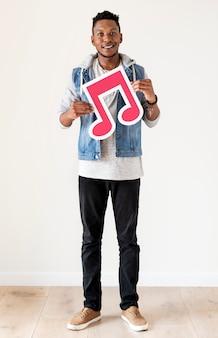 Afrikanischer mann, der eine ikone der musikalischen anmerkung hält