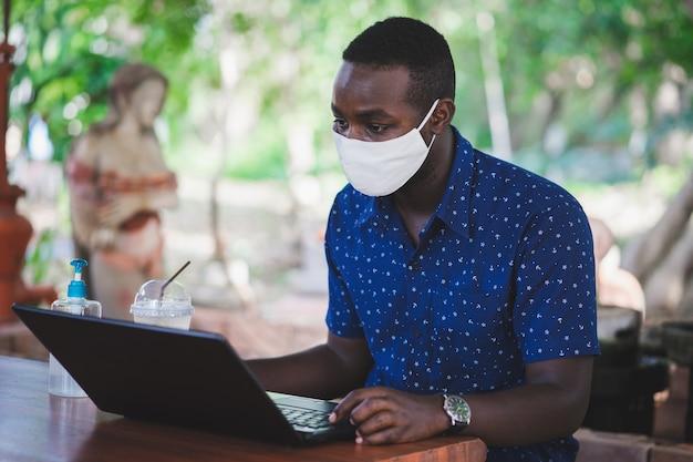 Afrikanischer mann, der eine maske trägt und einen laptop zu hause benutzt. whf oder work from home-konzept