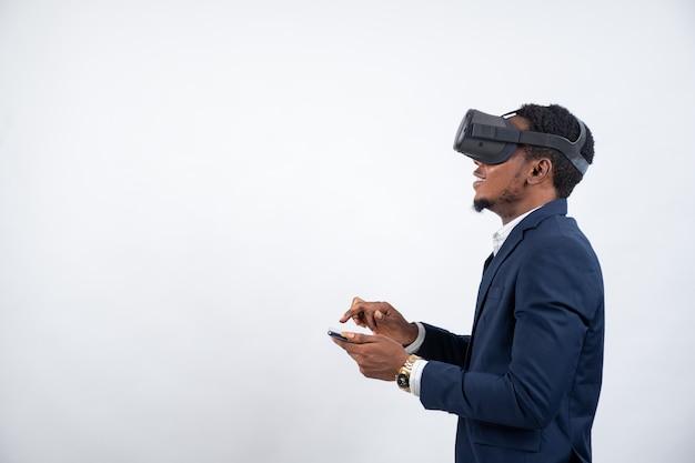 Afrikanischer mann, der einen anzug trägt und ein virtual-reality-headset und ein telefon verwendet