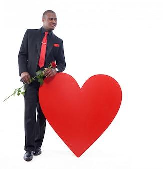 Afrikanischer mann, der elegante suite posiert, wegschaut und lächelt, rote rose in der hand hält und großes rotes herz lehnt.