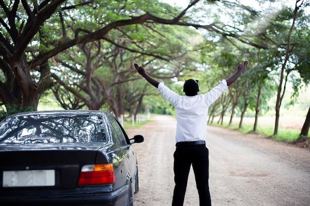 Afrikanischer mann der freiheit, der eine weiße hemd- und sonnenbrillestellung trägt