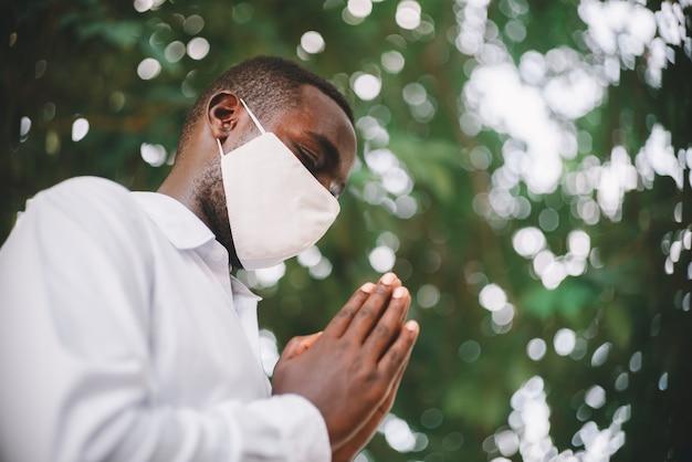 Afrikanischer mann, der für gott mit tragender gesichtsmaske betet