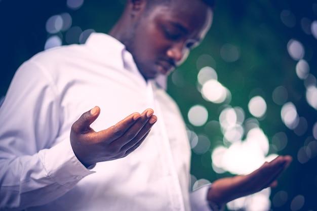 Afrikanischer mann, der für gott sei dank betet.