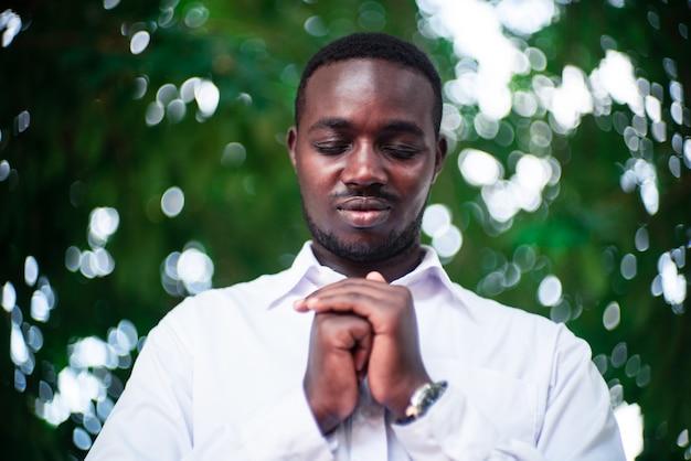 Afrikanischer mann, der für gott sei dank mit dem lächeln in der grünen natur betet
