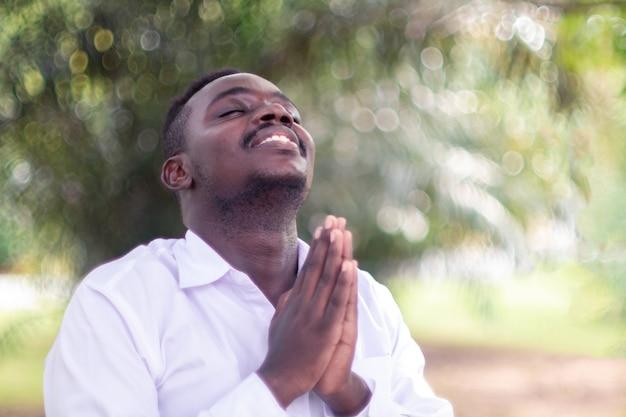 Afrikanischer mann, der für gott sei dank mit der grünen natur betet
