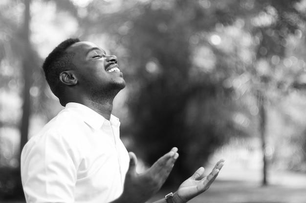 Afrikanischer mann, der für gott sei dank mit nahem auge betet