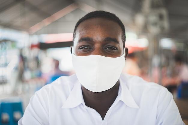 Afrikanischer mann, der gesichtsmaske mit weißem hemd trägt