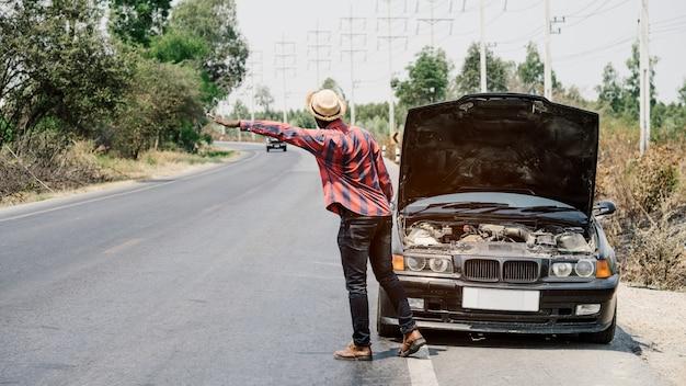 Afrikanischer mann, der hände für hilfe anhebt, weil sein auto seite die landstraße defekt ist