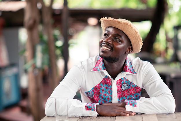 Afrikanischer mann, der hut und einheimisches tuch traditionell bunt mit denken trägt