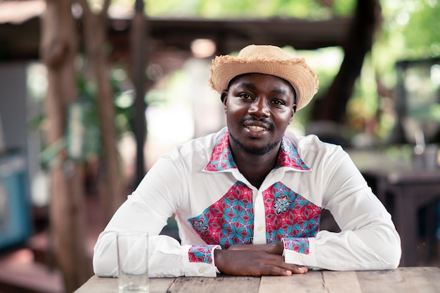 Afrikanischer mann, der hut und einheimisches tuch traditionell bunt mit lächeln und glücklich trägt.