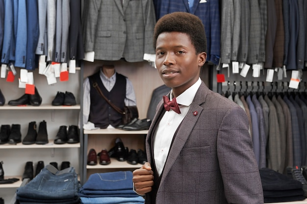 Afrikanischer mann, der in der boutique im weißen hemd, im stilvollen anzug aufwirft.