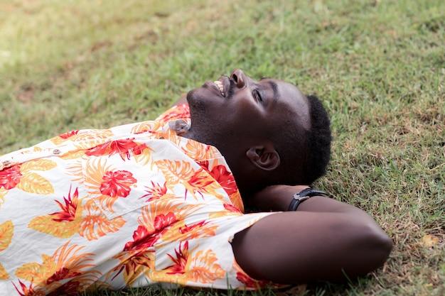 Afrikanischer mann, der inmitten der natur mit glück und trost auf dem boden liegt