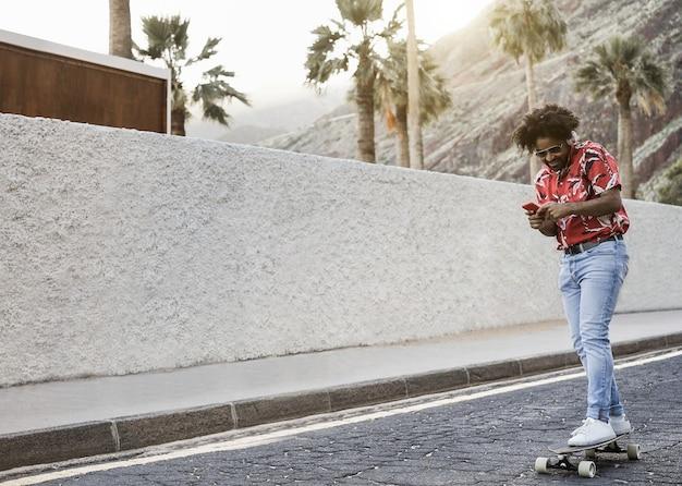 Afrikanischer mann, der longboard auf der straße mit palmen im hintergrund reitet - fokus auf gesicht