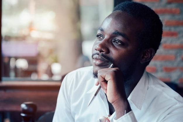 Afrikanischer mann, der mit dem halten einer wanne denkt und schaut.