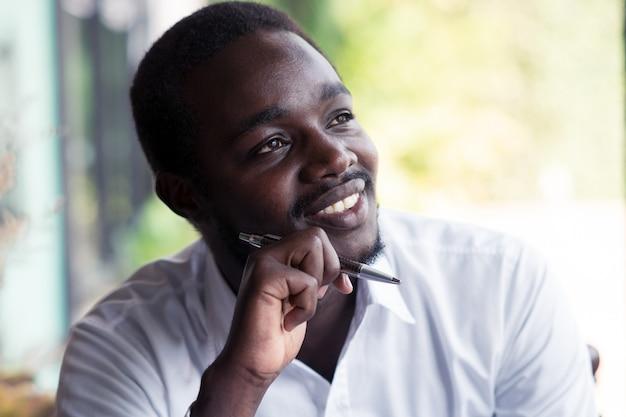 Afrikanischer mann, der mit dem halten eines stiftes denkt und schaut.