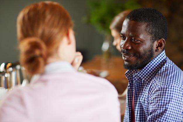 Afrikanischer mann, der mit frau im cafe spricht