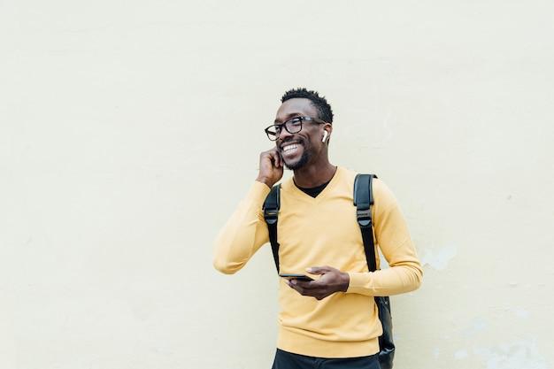 Afrikanischer mann, der musik durch kopfhörer hört. er setzt den kopfhörer auf sein ohr.