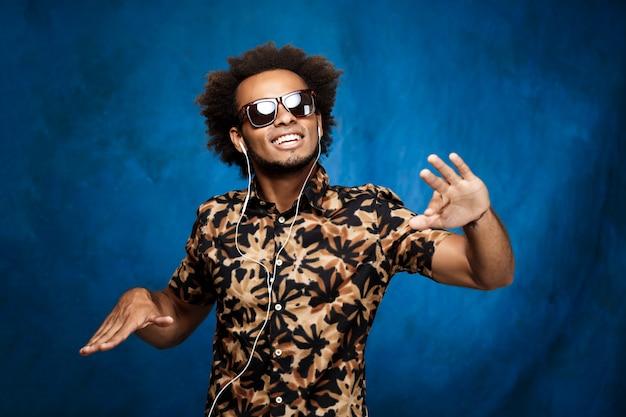 Afrikanischer mann, der musik in den kopfhörern hört und über blaue wand tanzt.