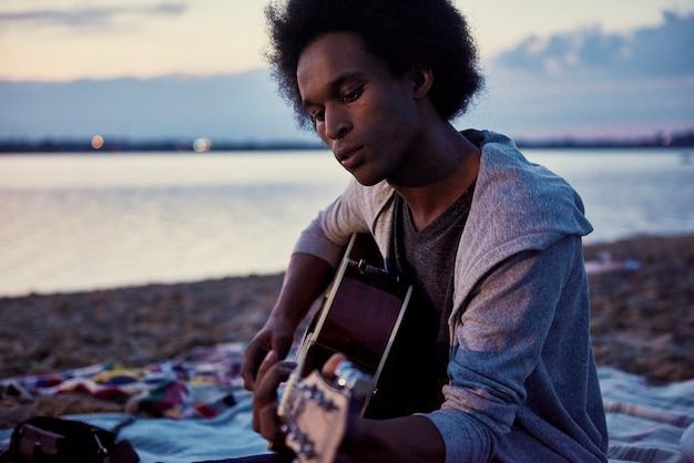 Afrikanischer mann, der nachts am strand gitarre spielt