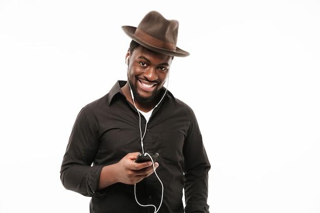 Afrikanischer mann, der per telefon plaudert und musik hört