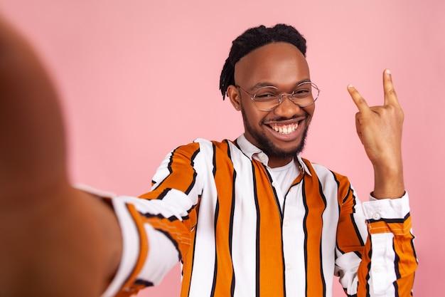 Afrikanischer mann, der rock'n'roll-geste mit den fingern zeigt, vor der selfie-kamera posiert, live-stream