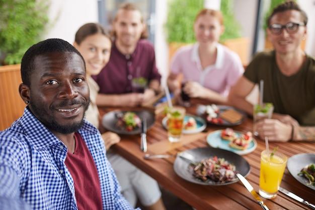 Afrikanischer mann, der selfie-foto mit freunden im cafe macht