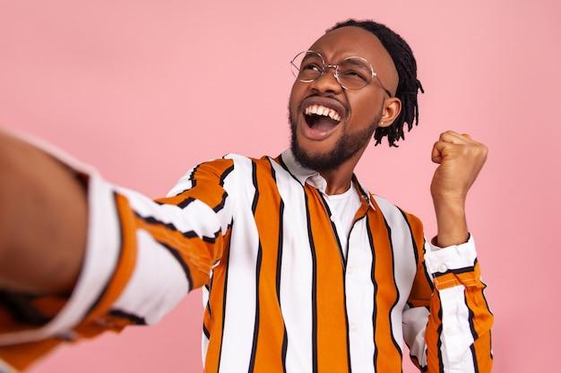 Afrikanischer mann, der sich freut, eine ja-geste zu machen, vor der selfie-kamera posiert und den gewinn des werbegeschenks genießt