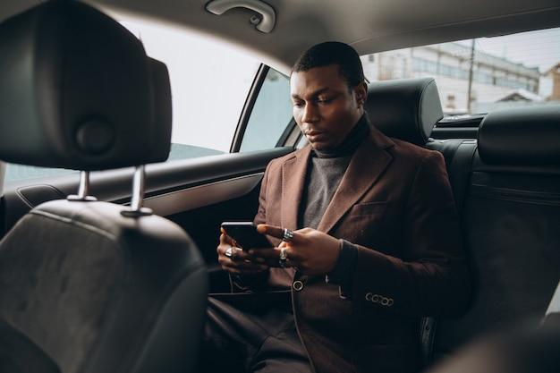 Afrikanischer mann, der smartphone beim sitzen auf rücksitz im auto verwendet.