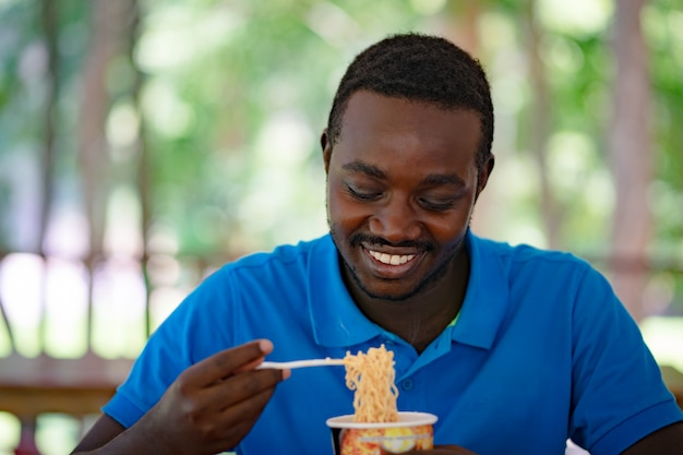 Afrikanischer mann, der sofortige nudelsuppe für das mittagessen isst