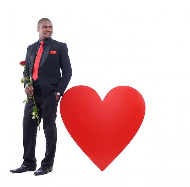 Afrikanischer mann, der vom großen verzierten roten herzen lehnt und rote rose hält