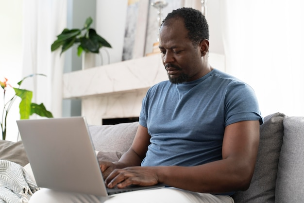 Afrikanischer mann, der von zu hause aus arbeitet