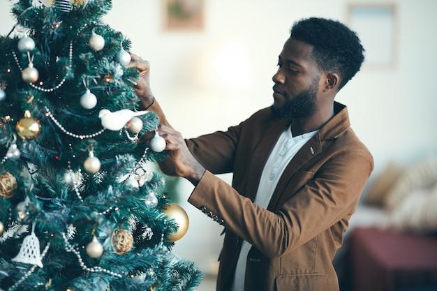 Afrikanischer mann, der weihnachtsbaum verziert