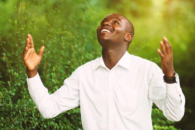 Afrikanischer mann des lächelns, der für gott sei dank betet.